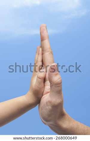 Father and son in high five gesture on a sky with clouds background  - stock photo