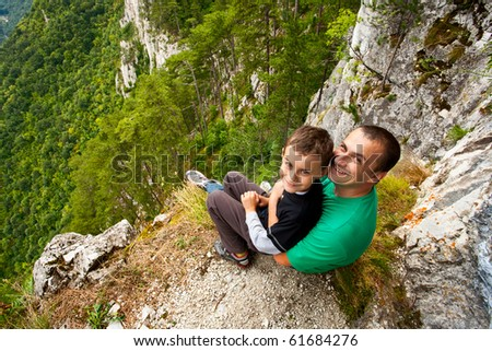 Father and son in mountains, sitting on the edge of a cliff - stock photo