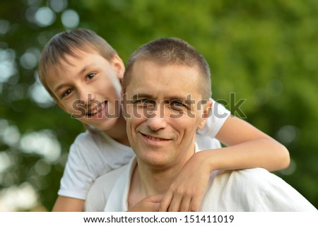 Father and son in nature in summer park - stock photo