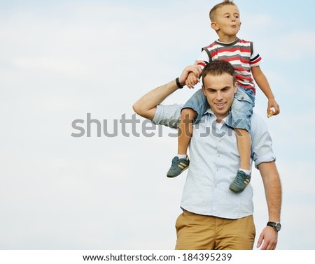Father and son in nature walking piggyback on shoulders - stock photo