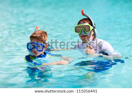 Father and son in ocean prepare for snorkeling
