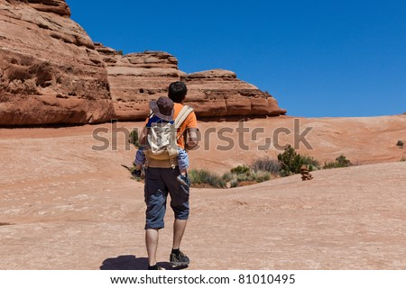 father and son in the baby carrier hiking - stock photo