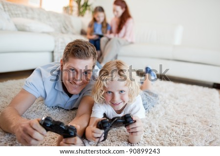Father and son in the living room playing video games together - stock photo