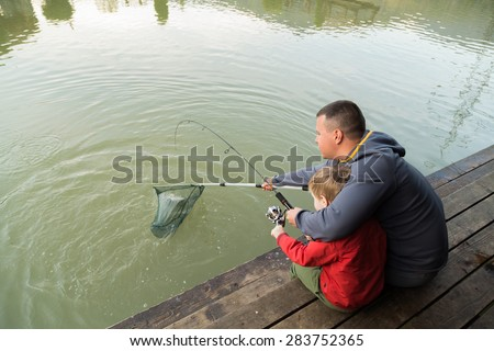 Father and son in the process of catching fish on the lake. Fish on the hook. Happy childhood child. Loving father. Family fishing. - stock photo