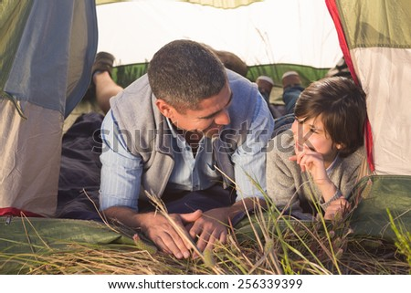Father and son in their tent on a sunny day