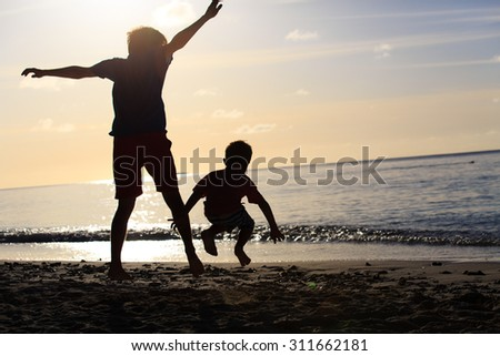 father and son jumping at sunset beach, happy family - stock photo