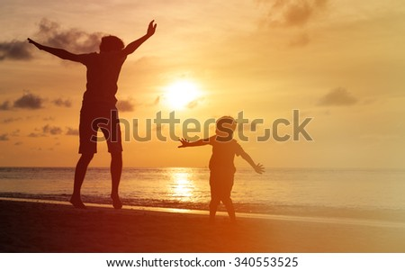 father and son jumping at sunset beach, happy family