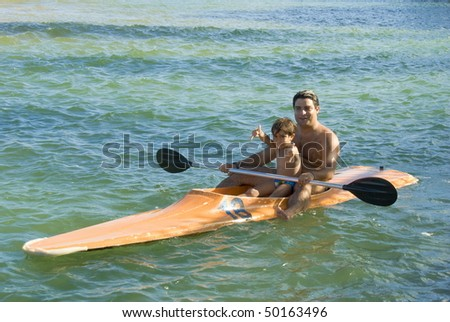 Father and son kayaking in the water. - stock photo