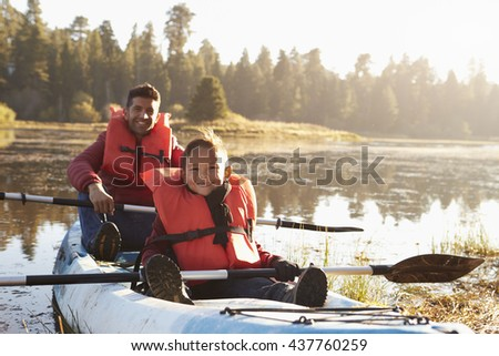 Father and son kayaking on rural lake, close up - stock photo