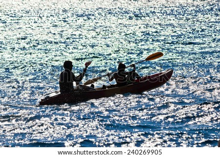 Father and son kayaking silhouette at sea - stock photo