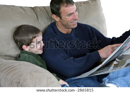 Father and son laughing reading the paper together