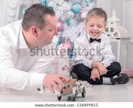 Father and son lay near Christmas tree, smiling, happy, playing with model cars. New year