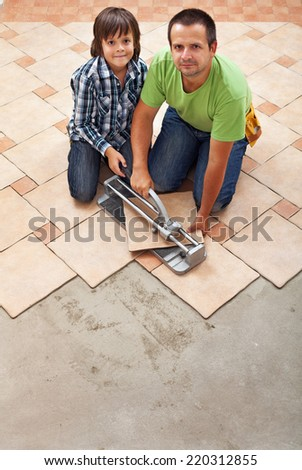 Father and son laying ceramic floor tiles together - working with a cutter - stock photo