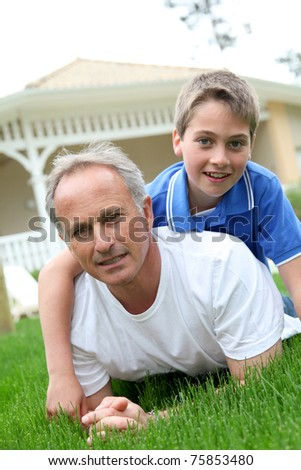 Father and son laying down in house garden - stock photo