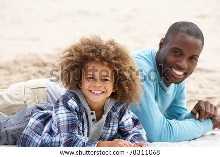 Father and son laying on beach