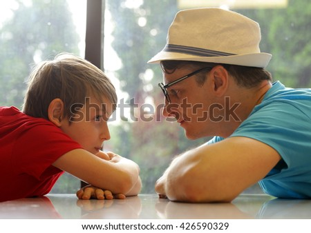 father and son look at each other, family and happiness - stock photo