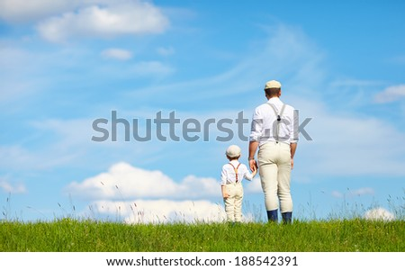 father and son look beyond the horizon - stock photo