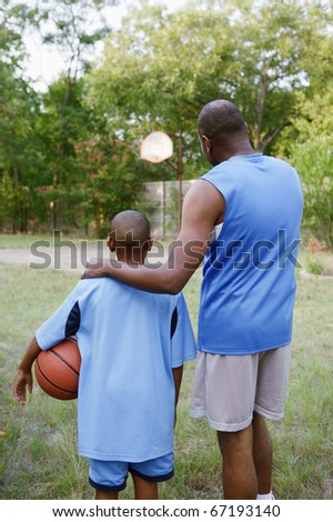 Father and son looking at basketball court - stock photo