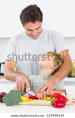 Father and son looking at each other as they are chopping vegetables in the kitchen