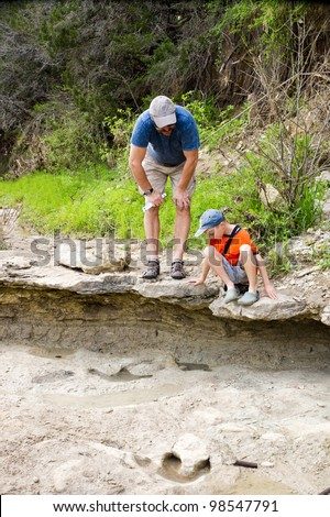 Father and son looking at fossilized dinosaur footprints. Dinosaur Valley State Park, Glen Rose, Texas - stock photo