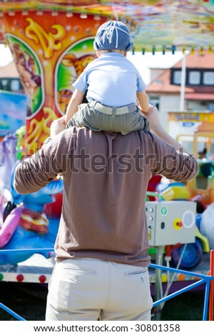 Father and son looking at merry-go-round - stock photo