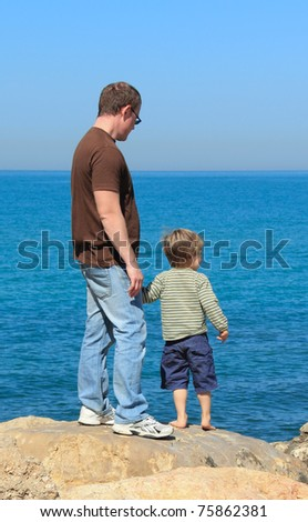 father and son looking at sea - stock photo