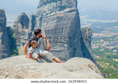 Father and son looking at the town of Kalambaka bird's eye view. Meteora, Greece. - stock photo