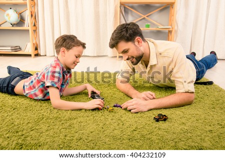 Father and son  lying on carpet and playing with toy cars - stock photo