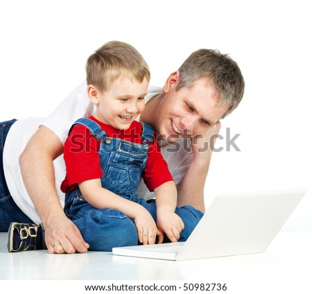 Father and son lying on the floor with notebook - stock photo