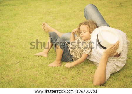 father and son lying on the grass at the day time - stock photo