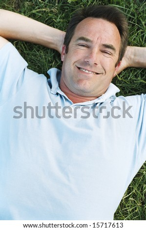 Father and son lying outdoors sleeping - stock photo