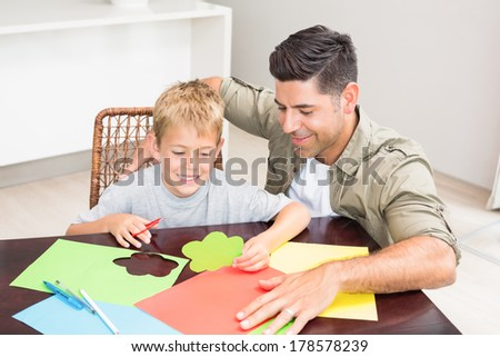 Father and son making paper shapes together at the table at home in kitchen - stock photo