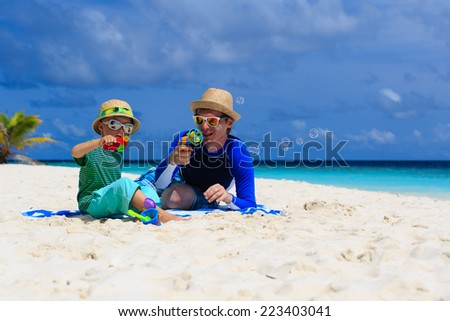 father and son making soap bubbles on tropical beach - stock photo