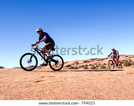 Father and son mountain bike near Moab, Utah - stock photo