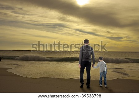 father and son on a beach facing the sea - stock photo