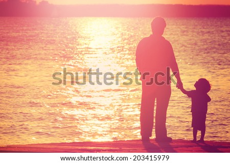 Father and son  on a dock at sunset, boy looking up at his father - stock photo