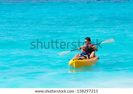 Father and son on a kayak ride in a tropical blue sea - stock photo