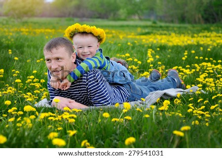 Father and son on a meadow in spring. - stock photo