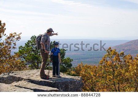 Father and son on a mountain top. A man shows at the landscape - stock photo