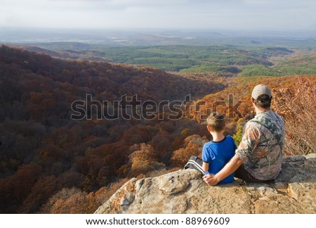 Father and son on a mountain top. A man shows at the landscape