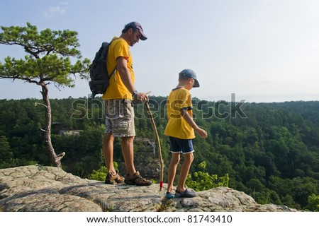 Father and son on a mountain top looking at the path - stock photo