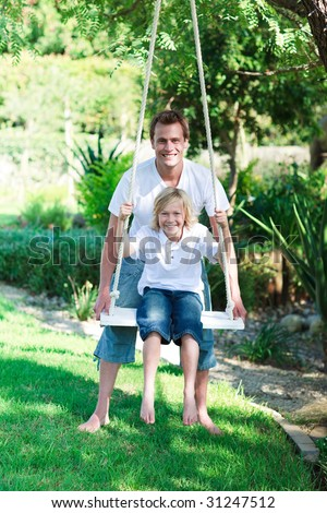 Father and son on a swing in a park - stock photo
