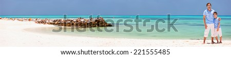 Father and son on a tropical beach vacation, panorama perfect for banner - stock photo