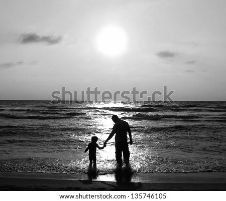 father and son on a walk by the sea at sunset. Black and white photo. - stock photo