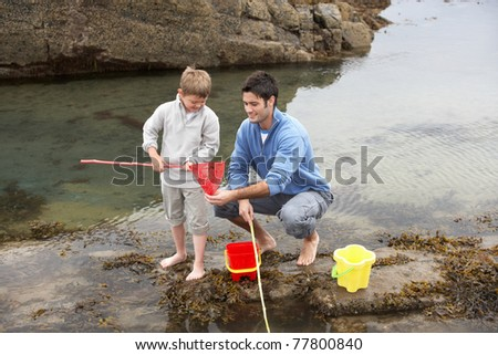 Father and son on beach - stock photo