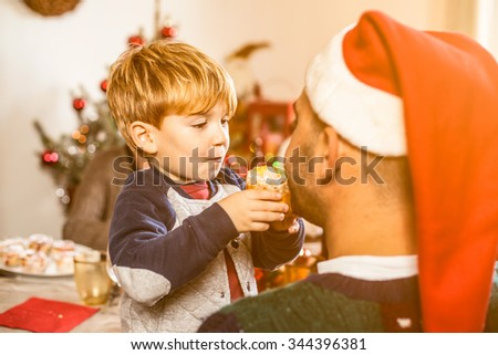 Father and son on Christmas Day. The child approaches the mouth of the father a small panettone to make it taste. The father has a red Christmas hat. Behind them on the table and the Christmas tree