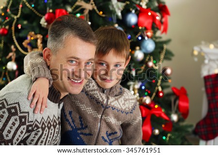 Father and son on Christmas interior background - stock photo