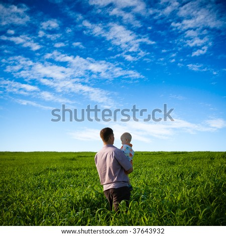 father and son on green field under blue skies - stock photo