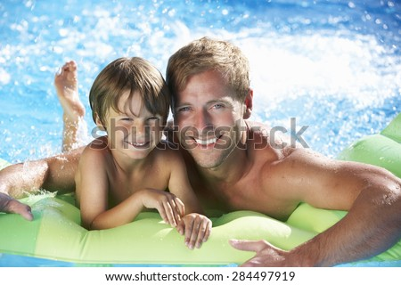 Father And Son On Holiday In Swimming Pool - stock photo