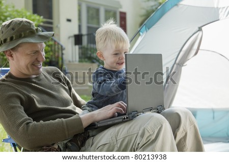 Father and son on laptop computer camping in the front yard - stock photo
